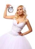 Braut mit Wecker. schöne blonde junge Frau, die auf den Bräutigam lokalisiert wartet Stockfoto