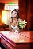 Braut nahe bei dem Klavier stockbild