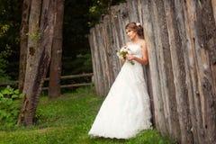 Braut nahe hölzernem rustikalem Zaun im Park lizenzfreies stockbild