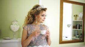 Braut nimmt einen Tasse Kaffee von der Kamineinfassung und nimmt ein Schlückchen stock video