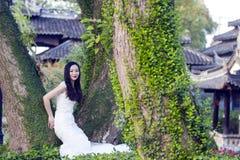 Braut portraint mit weißem Hochzeitskleid vor alten Bäumen und Altbau Stockbild