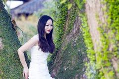 Braut portraint mit weißem Hochzeitskleid vor alten Bäumen und Altbau Stockfotos