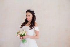 Braut-Prinzessin steht in einem Hochzeitskleid mit Blumen Stockbilder