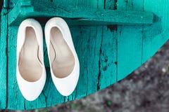 Braut ` s biege Schuhe auf Ferse auf einer tiffany Farbe des hölzernen Brettes stockfoto