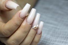 Braut ` s Hände mit einfacher Maniküre mit einem kleinen Juwel auf dem Na lizenzfreies stockfoto