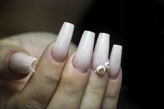 Braut ` s Hände mit einfacher Maniküre mit einem kleinen Juwel auf dem Na lizenzfreie stockfotos
