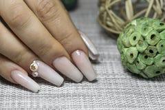 Braut ` s Hände mit einfacher Maniküre mit einem kleinen Juwel auf dem Na stockbild