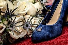 Braut ` s Verpflichtung Ring Resting auf ihren blauen Veloursleder-Hochzeits-Schuhen Stockbilder