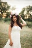 Braut Schöne junge blonde Frau im Park mit Blumenkranz und Blumenstrauß an einem warmen Sommertag Lizenzfreie Stockfotos