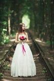 Braut Schöne junge blonde Frau im Park mit Blumenkranz und Blumenstrauß an einem warmen Sommertag Lizenzfreies Stockbild