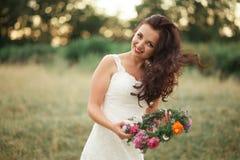 Braut Schöne junge blonde Frau im Park mit Blumenkranz und Blumenstrauß an einem warmen Sommertag Stockbild