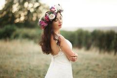 Braut Schöne junge blonde Frau im Park mit Blumenkranz und Blumenstrauß an einem warmen Sommertag Lizenzfreie Stockfotografie