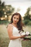 Braut Schöne junge blonde Frau im Park mit Blumenkranz und Blumenstrauß an einem warmen Sommertag Stockbilder