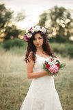 Braut Schöne junge blonde Frau im Park mit Blumenkranz und Blumenstrauß an einem warmen Sommertag Lizenzfreies Stockfoto