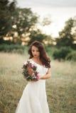 Braut Schöne junge blonde Frau im Park mit Blumenkranz und Blumenstrauß an einem warmen Sommertag Stockfotos