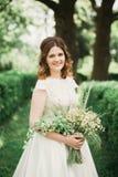 Braut Schöne junge blonde Frau im Park mit Blumenkranz und Blumenstrauß an einem warmen Sommertag Stockfotografie