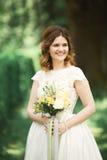 Braut Schöne junge blonde Frau im Park mit Blumenkranz und Blumenstrauß an einem warmen Sommertag Stockfoto