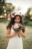 Braut Schöne junge blonde Frau im Park mit Blumenkranz und Blumenstrauß an einem warmen Sommertag Lizenzfreie Stockbilder