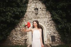 Braut Schöne junge Frau im Park mit Blumenstrauß an einem warmen Sommertag Stockfotografie