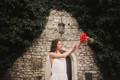 Braut Schöne junge Frau im Park mit Blumenstrauß an einem warmen Sommertag Lizenzfreie Stockbilder