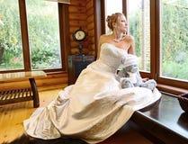 Braut schaut aus dem Fenster heraus Stockfotografie