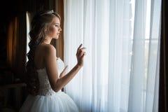 Braut schaut aus dem Fenster, Hochzeitstag heraus Lizenzfreies Stockfoto