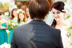 Braut schaut das bezauberte Hören auf den Eid des Bräutigams Lizenzfreie Stockfotos