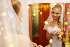 Braut schaut im Spiegel Stockbild