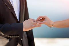 Braut setzt einen Ring auf die Hand des Bräutigams stockfotografie