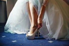 Braut setzt sich auf weiße Schuhe in Vorbereitung auf die Hochzeit lizenzfreie stockbilder