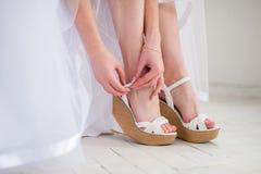 Braut setzt weiße Schuhe für die Heirat Stockfoto