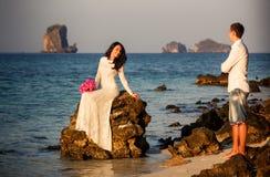 Braut sitzt auf Felsenbräutigamständen auf Strand Lizenzfreies Stockfoto