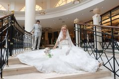 Braut sitzt auf Treppenhaus. Hinter ihr ist zurück Bräutigam Stockbild