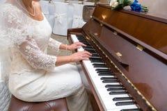 Braut spielt Klavier Stockfotografie