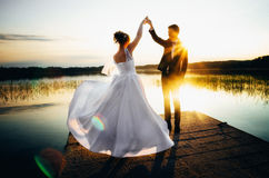 Braut spinnt in ein weißes Kleid, das Hand der Bräutigam auf der Bank des Sees bei Sonnenuntergang hält Lizenzfreie Stockfotos