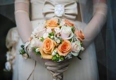 Braut steht im Kleid, Bogen auf Taille hält Blumenstrauß lizenzfreies stockfoto