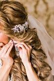 Braut trägt Ohrringe Stockbild
