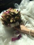 Braut- und Blumenhintergrundbrautkleid und Perlenhalskette stockfoto