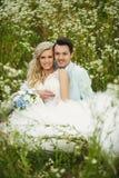 Braut und Bräutigam auf dem Gras Lizenzfreie Stockbilder