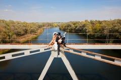 Braut und Bräutigam auf der Brücke über dem Fluss   Lizenzfreies Stockbild