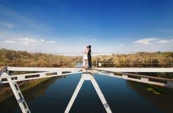 Braut und Bräutigam auf der Brücke über dem Fluss Stockfotos