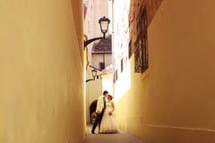 Braut und Bräutigam auf einer schmalen Straße Stockbild