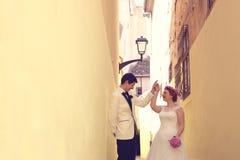 Braut und Bräutigam auf einer schmalen Straße Lizenzfreie Stockfotos