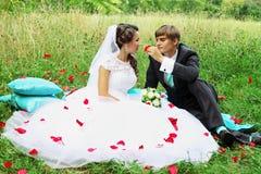 Braut und Bräutigam in den rosafarbenen Blumenblättern lizenzfreie stockfotos