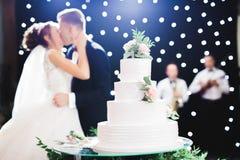 Braut und Bräutigam an der Hochzeit, welche die Hochzeitstorte schneidet stockbilder