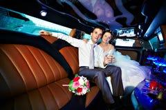 Braut und Bräutigam in der Hochzeitslimousine Stockbild