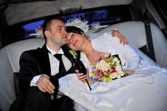 Braut und Bräutigam in der Limousine Stockbilder