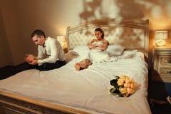 Braut und Bräutigam, die auf Bett liegen Lizenzfreie Stockfotos