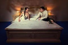 Braut und Bräutigam, die auf Bett liegen Stockbild