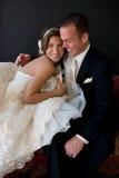 Braut und Bräutigam, die auf Couch sitzen Lizenzfreies Stockfoto